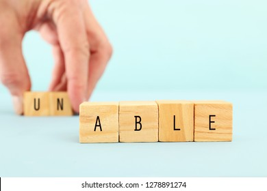man hand spelling the text unable with wooden cubes, taking out the word un so it written able. success and challenge concept
