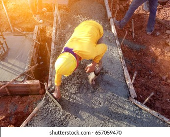 man hand spreading concrete mix with trowel in foundation. A construction worker is pouring cement and concrete,Selective focus.Workers are plastering the foundations of large buildings.