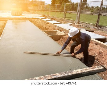 man hand spreading concrete mix with trowel in foundation. A construction worker is pouring cement and concrete,selective focus and Film Tone with Light fair.Foreman freshly poured concrete.