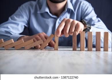 Man hand Stopping falling wooden blocks. Risk, Management, Solution