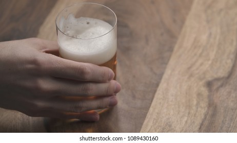 man hand take ginger beer in a glass on wood table