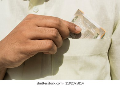 Man hand takes a indian currency out of his pocket close up