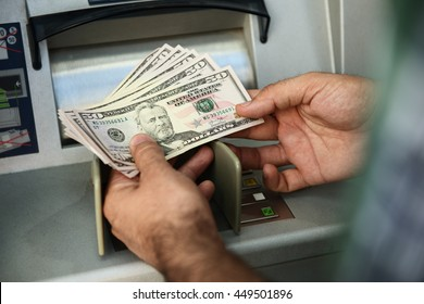 Man hand taking dollar bills out of an ATM