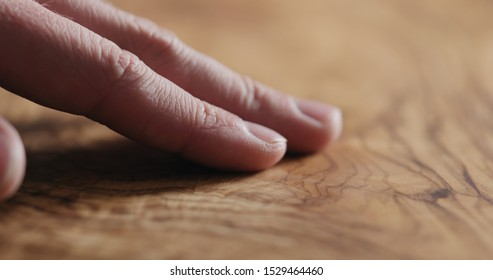 man hand touch oil finished olive wood surface