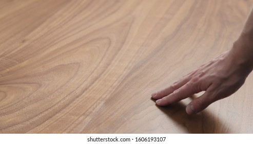 man hand touches black walnut dining table surface