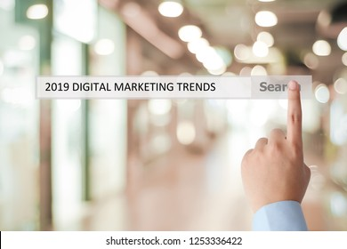 Man hand touching 2019 digital marketing trends on search bar over blur office background, banner, 2019 business strategy annual plan, success in business concept