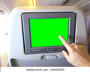 Man hand touching the Green background  lcd  at airplane.