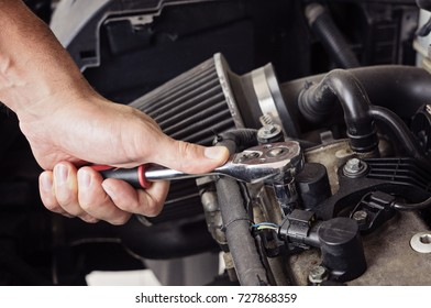 A man hand unscrews the spark plugs in the car close up, toned blue