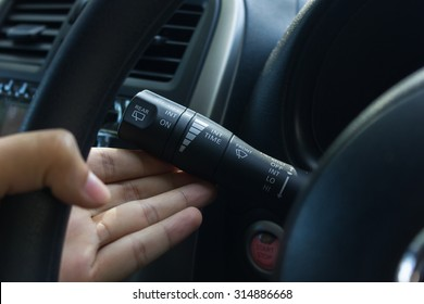 man hand use the signal switch. Car interior detail with blue light.