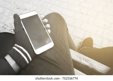 Man hand using a smart phone outdoors. The man sitting and wait for the meeting with a person . Black and white