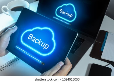 Man hand using Tablet and notebook computer to sync data to cloud backup technology