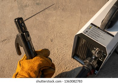 Man hand wearing orange leather gloves holding black electrode holder with white welding machine beside on concrete floor and natural sunlight.