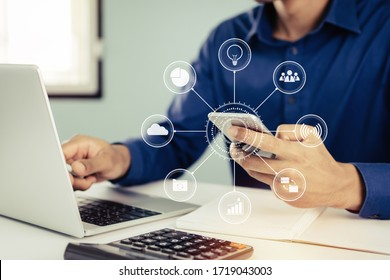 man hand working about financial on mobile phone with virtual digital icon, laptop computer and report on desk at home office, digital marketing, work from home, business finance, technology concept - Shutterstock ID 1719043003