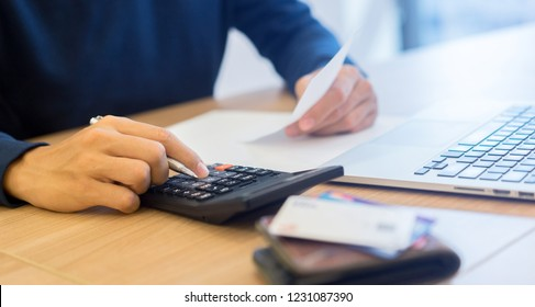 man hand write on notebook and calculate on calculator about debt bills pay monthly at the table in office and manage expense payroll for money risk and crisis financial and work from home concept