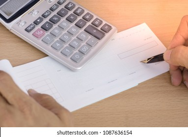 Man hand  writing cheque book for payment with calculator on the wooden table.