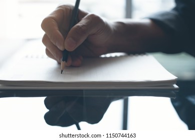 Man hand writing on papaer notebook with a pencil. Man taking note or make a plan on notepad with reflection on office desk at home, copy space, close up