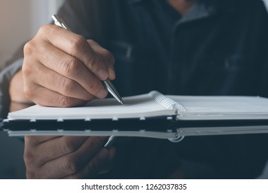 Man hand writing on papaer notebook with a pen. Man taking note or make a plan on notepad with reflection on office desk, close up, dark tone