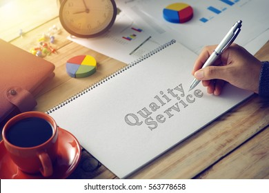 Man hand writing word quality service