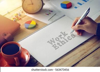 Man hand writing word work ethics
