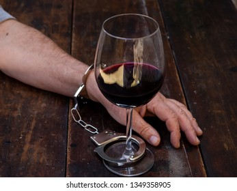 A man handcuffed to a glass of red wine. Alcohol addiction or alcoholism concept