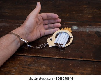 A man handcuffed to a handful of cigarettes. Tobacco addiction concept