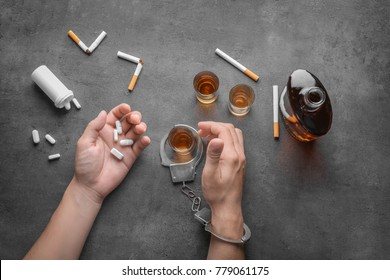 Man in handcuffs with cigarettes, drugs and alcohol at table. Concept of bad habits