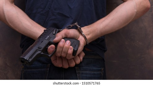 a man in handcuffs holding a gun in his hands behind his back