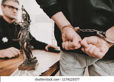 A Man In Handcuffs Stands In Front Of Policeman. Femida Statue. Work Together. Ask A Question. Citizen's Protection. Detainee Arrest. Public Order. Crime Scene. Suspect Questionee.