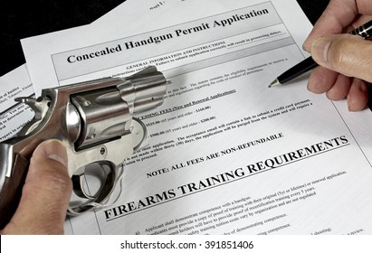 man with handgun firearm pistol and concealed carry permit application