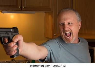 Man with handgun in kitchen, Gun in focus only, trigger finger in the register position