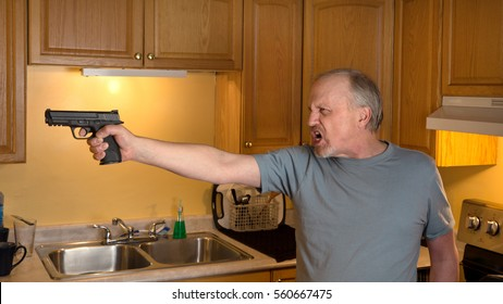 Man with handgun in kitchen, Gun in focus only, trigger finger in the register position