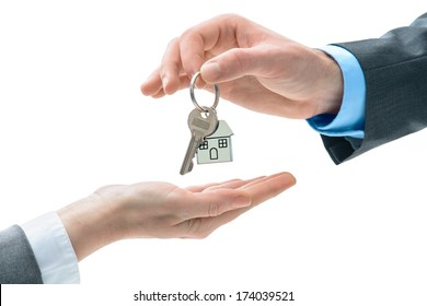 Man is handing a house key to other hands. Concept of real estate and deal