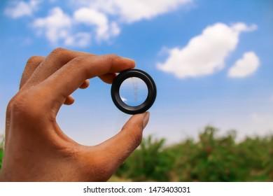 man handing a mobile lens and see blue sky,blue sky ,top view of sky, sky background,lens