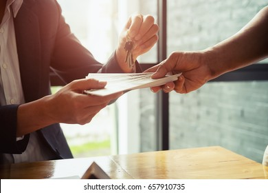 Man is handing money to real estate agent gives house keys to his client after signing contract