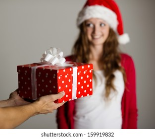 Man handing red wrapped gift to a beautiful woman