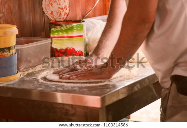 Man handle prepare pizza dough in bakery.