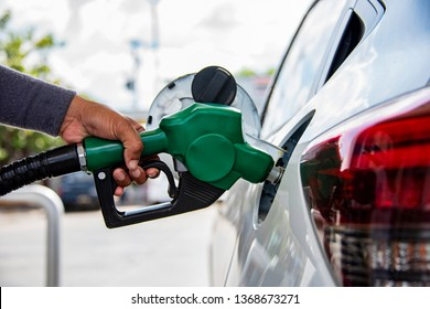 Man Handle pumping gasoline fuel nozzle to refuel. Vehicle fueling facility at petrol station. White car at gas station being filled with fuel. Transportation and ownership concept.