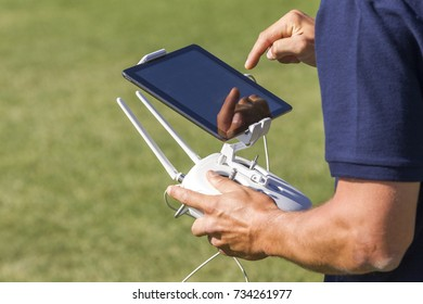 A man handle remote control of drone during capturing photos and video.