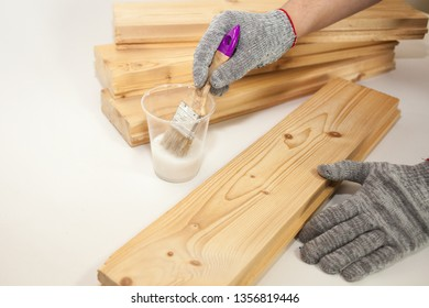The man handles the Board primer. Processing of pine boards, biosecurity, fire protection. Technology and production Create fotofone