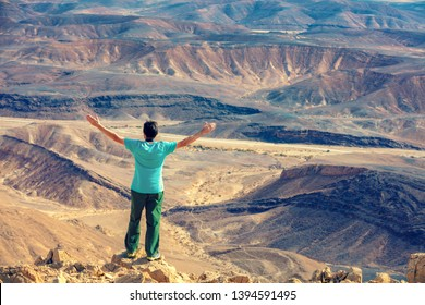 A man with hands in the air standing on the cliff in desert