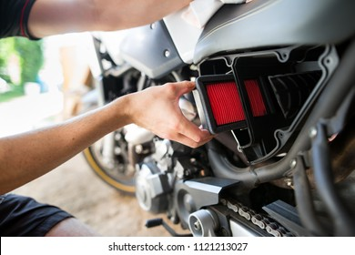 Man hands changing the air filter on his motorbike, doing maintenance