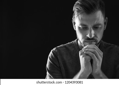 Man with hands clasped together for prayer on dark background, black and white effect. Space for text