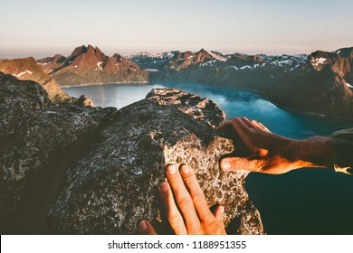 Man hands climbing up to mountain summit travel adventure active lifestyle extreme vacations in Norway