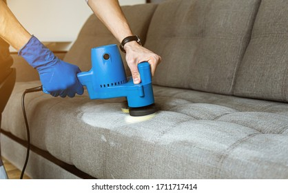 Man hands close up in in protective rubber glove, Dry cleaner's employee removing dirt from furniture in flat, closeup, vacuum clean sofa with professional equipment.