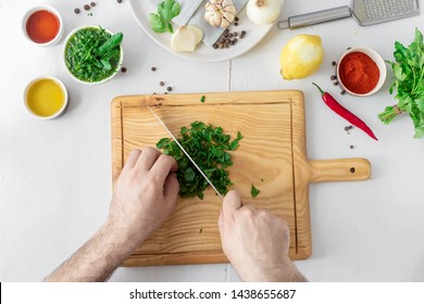 Man hands cooking above green Chimichurri or Chimmichurri salsa or sauce on white wooden table