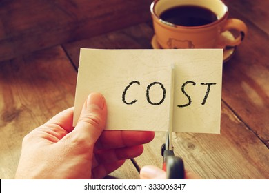 man hands cutting card with the word cost. business concept, cutting costs