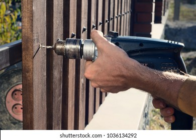 Man hands drilling wooden fence to metal construction. Building a wooden fence with a drill and screw. Close up of his hand and the tool in a DIY concept.