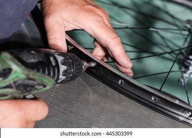 Man hands fixing bicycle rim in gray background. Repair shop, rim manufacturers