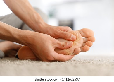 Man hands giving foot massage to yourself to relieve pain after a long walk, suffering with flat feet, close up, soft focus, indoors. Flat feet, leg fatigue.