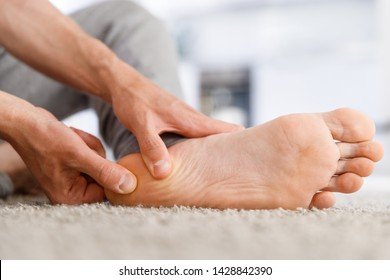 Man hands giving foot massage to yourself after a long walk, suffering from pain in heel spur, close up, indoors. Flat feet, leg fatigue, plantar fasciitis,